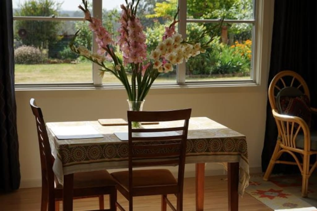 Dining table with outlook to garden and paddocks beyond.