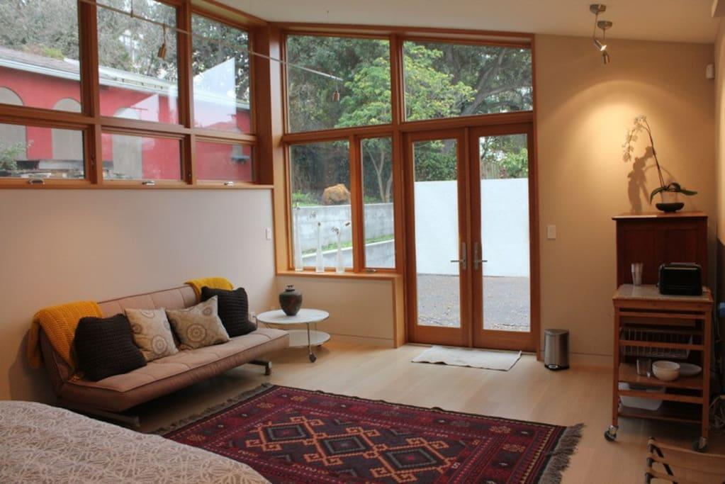 Spacious studio. Sofa on left. Kitchenette area on right.
