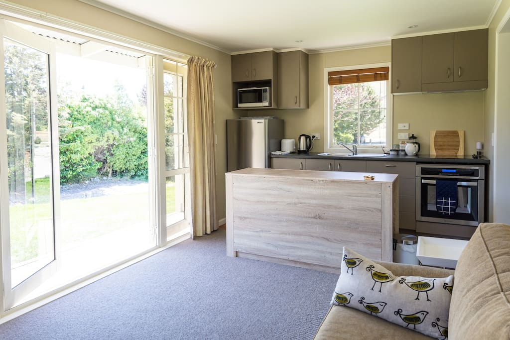 Living-kitchen with French doors opening onto deck and views