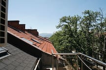 The beautiful view from the small balcony of the studio over the roofs of Plovdiv's centre and towards the mountains