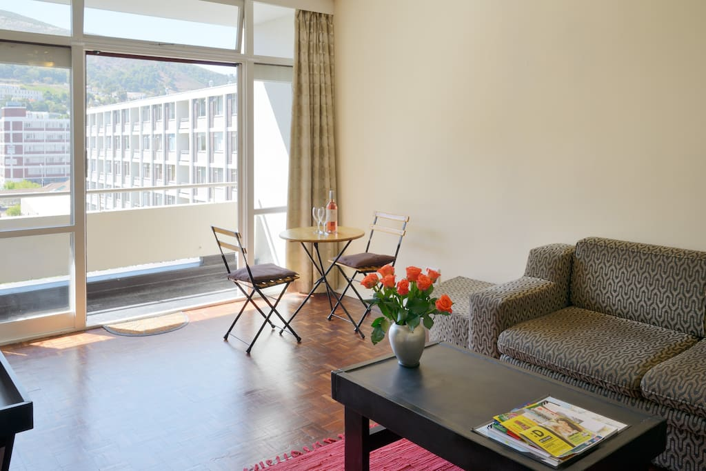 Open sunny  spacious living area with timber floors and balcony