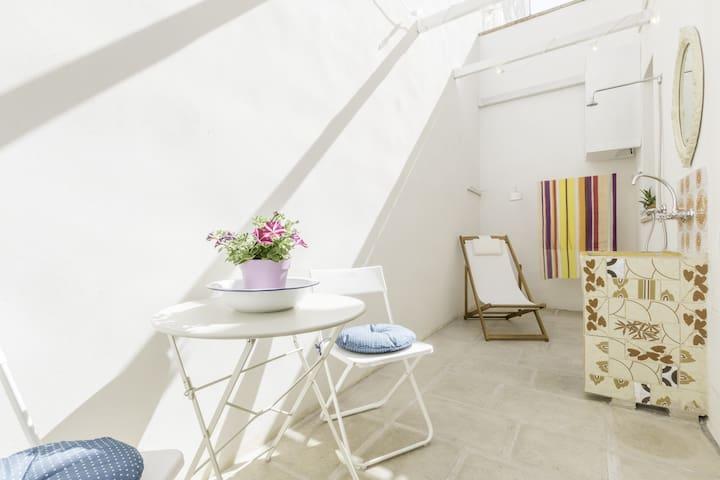 Veranda con tavolino, due sedie, sdraio, doccia esterna, lavandino con specchio e fili per il bucato