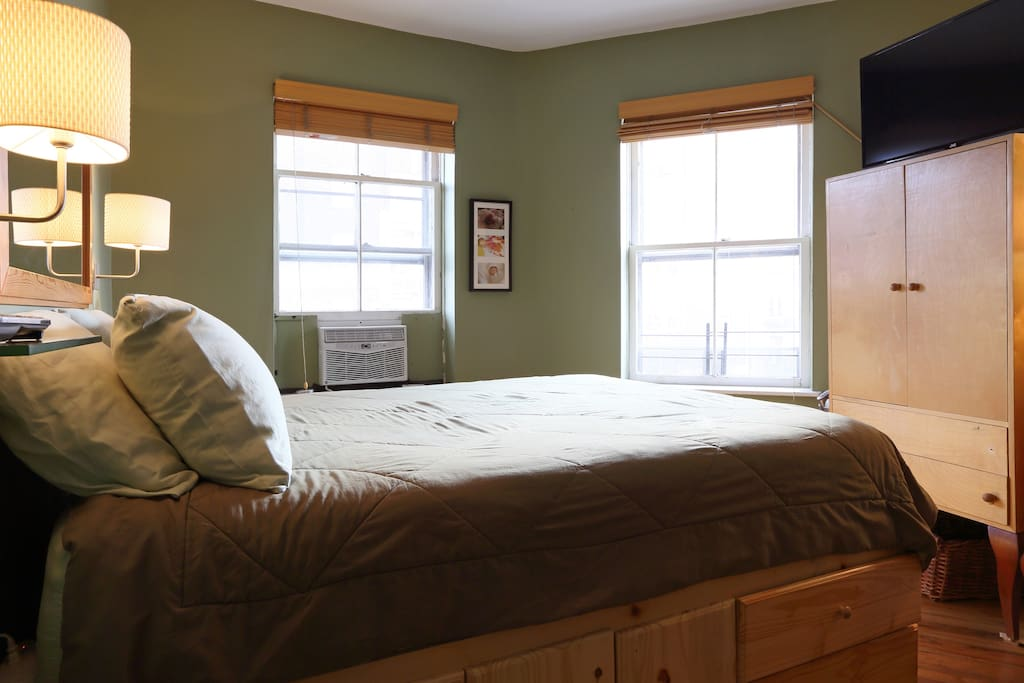 Main bedroom features a queen-size bed, two large windows and a 37-inch LED TV.