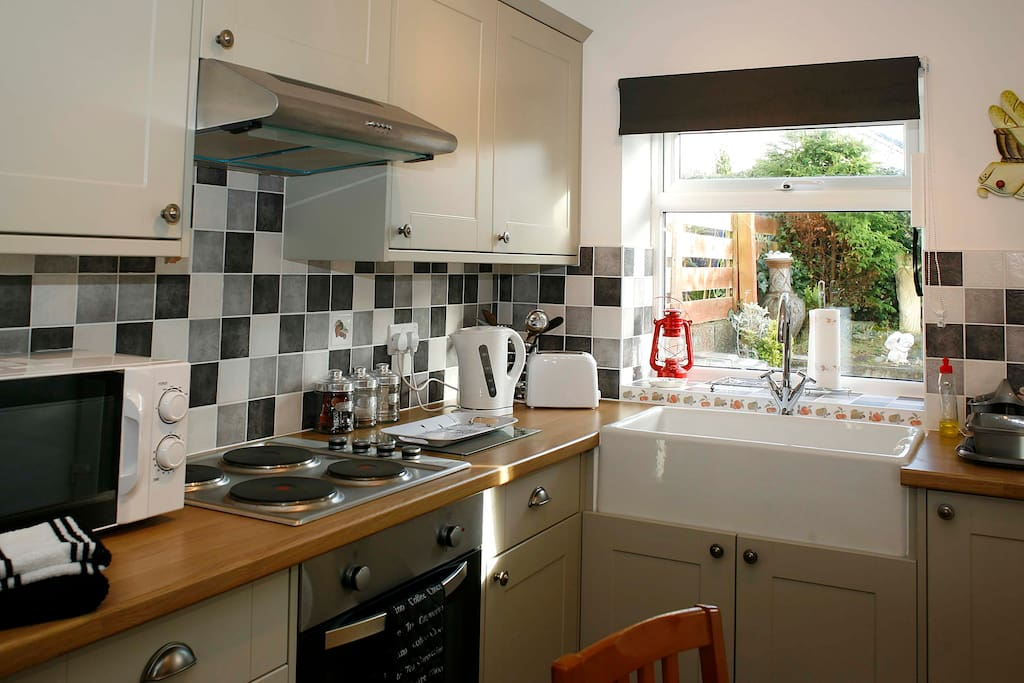 Modern units with electric cooker, hob, fridge, microwave, toaster and kettle.
