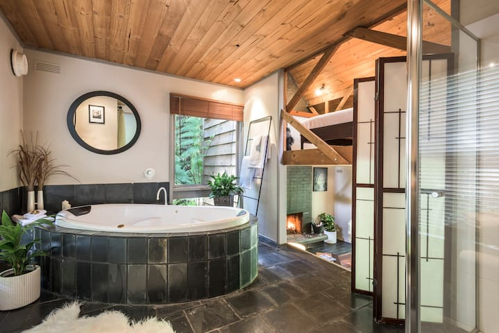 Bathroom with two person spa and separate walk in shower. It's on the middle level. You can see up to the mezzanine bedroom and down to the lounge