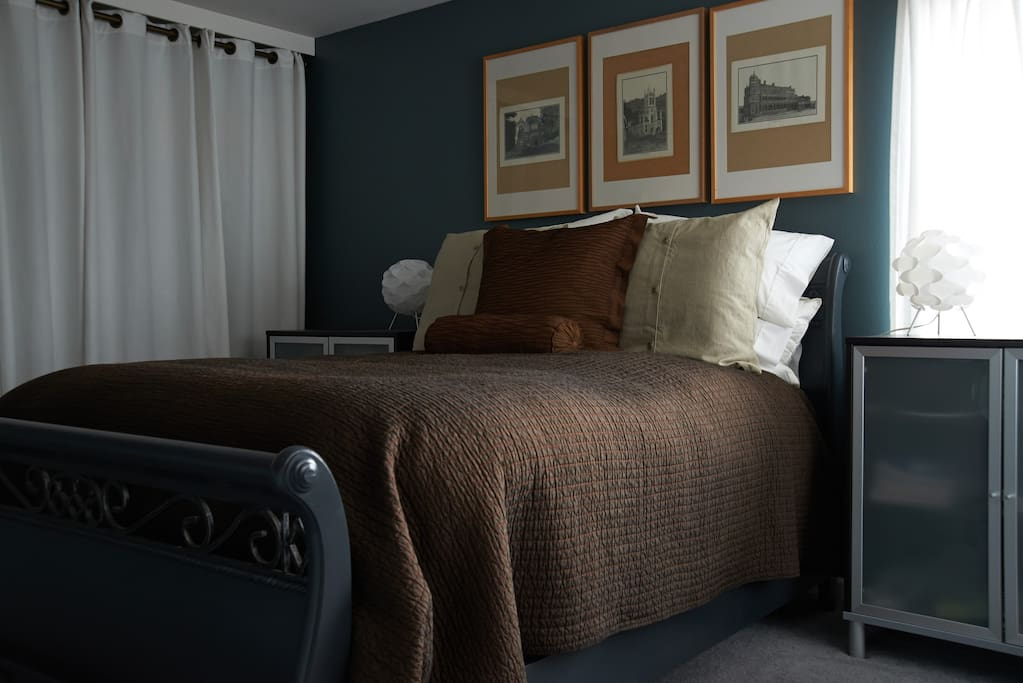 The bed is topped with a fluffy down duvet, cotton sheets, and lots of pillows.