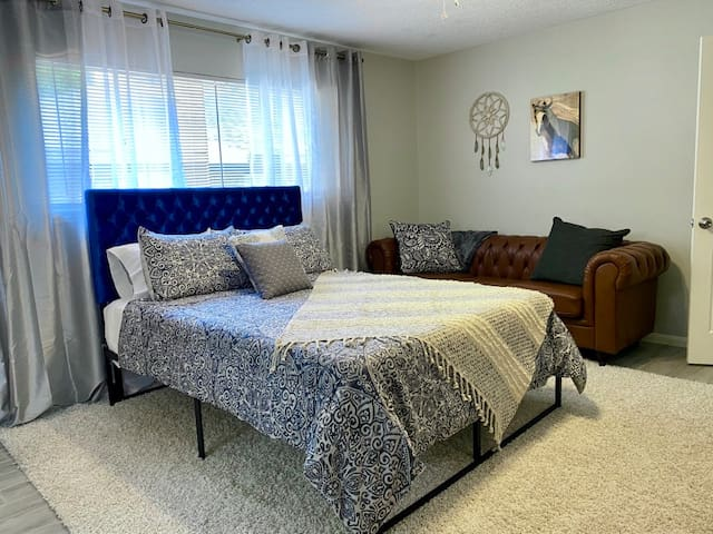 Master Bedroom with Queen Bed and lounge Couch with extra throws/pillows