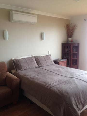 Queen size bed, bedside lamps, reverse cycle air conditioner and wall unit filled with books.