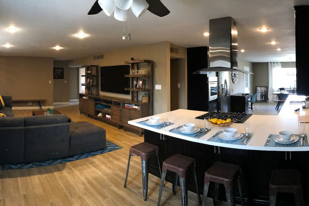 Living room with dining table and open concept kitchen. Kitchen has all appliances and breakfast bar.
