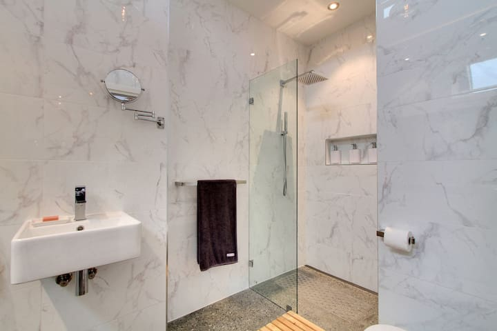 Stylish and roomy bathroom with polished concrete floor, floor to ceiling wall tiles and high quality stylish fittings.