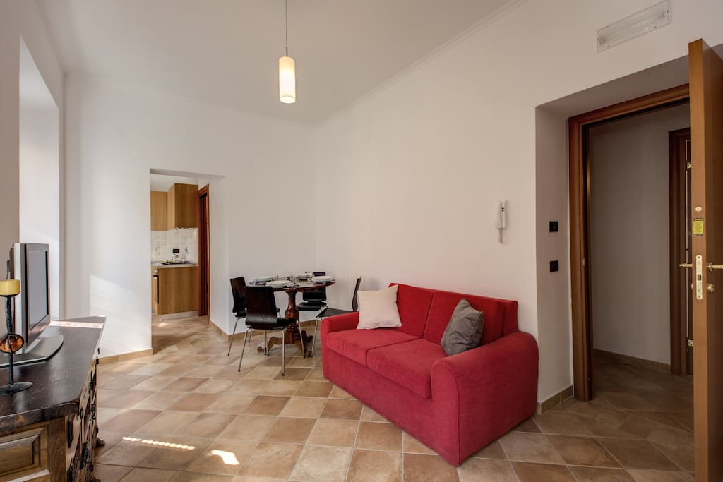 1st living room with French bed size sofa, TV, dinner table for four and air conditioning/heater. View of Via della Seggiola