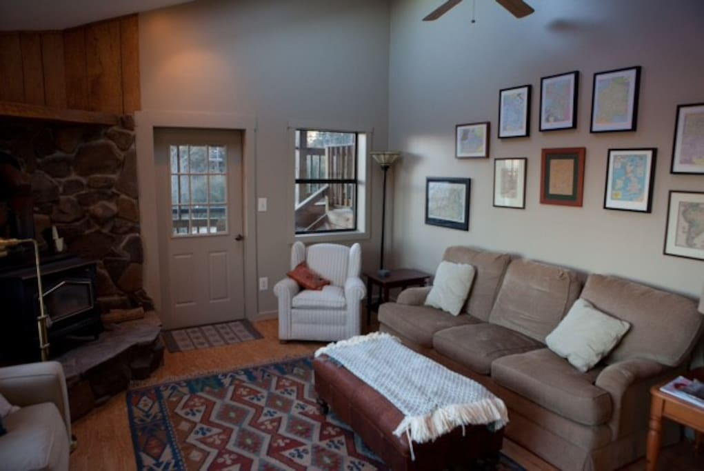 living area with two sofas (one a queen sleeper), wood stove, ceiling fan