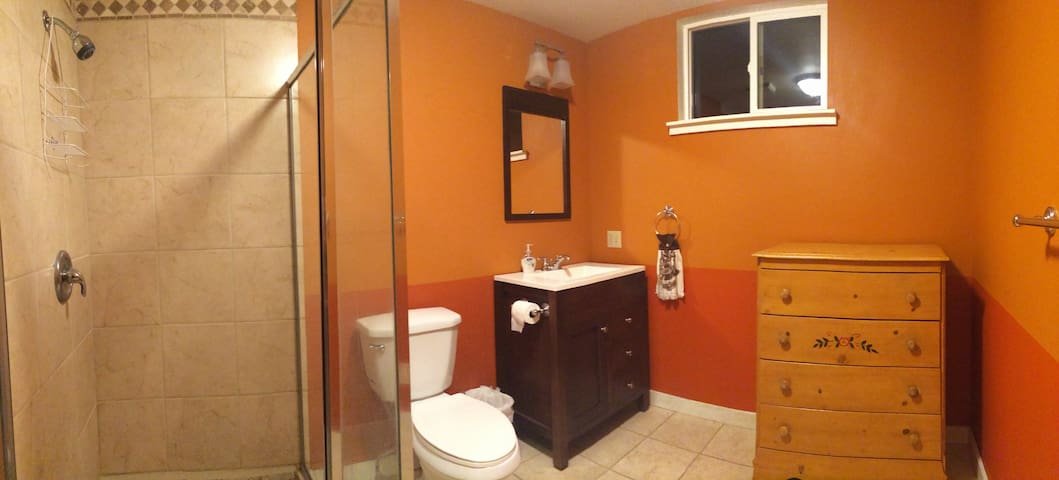 Large bathroom with tiled shower and floor.