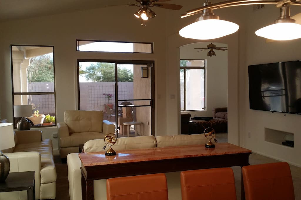 """Living room with 70""""  SmartTV, fast wireless Internet, Dining room seats 8 at glass and marble table. Den and backyard in background."""