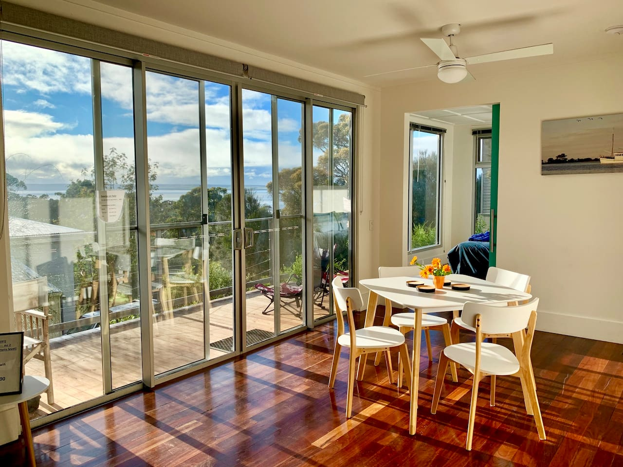 Winter sunlit self contained apartment with sea and bushland views showing dining area, decking entertainment area and entrance to master bedroom.