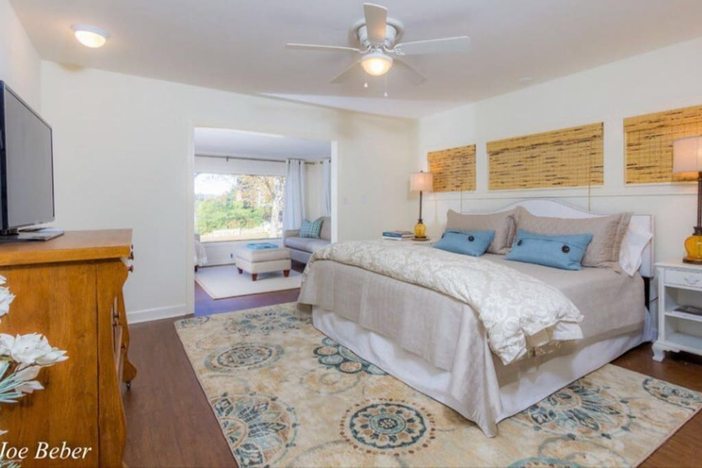 Large bedroom and attached sunroom have tv, patio access and water view.