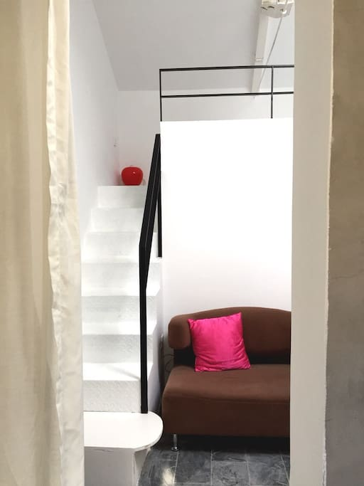 Sofa is big enough for two persons. Stairs lead to the bed on upper floor.
