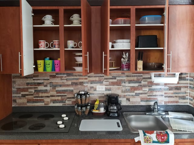 Full kitchen: coffee maker, microwave, toaster,  electric stove top, refrigerator, cooking accessories, , cutlery, glasses,  , blender,  and more.