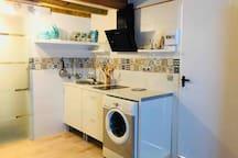 Zona de cocina, armarios de almacenaje, vitroceramica, campana extractora y el menaje necesario para que no falte de nada