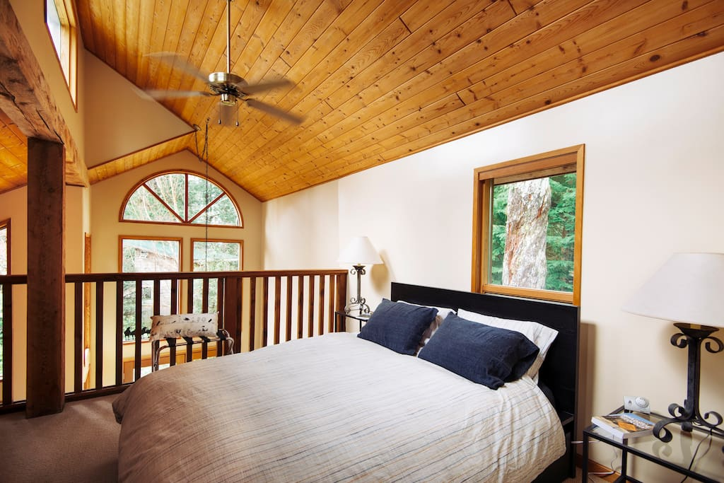 Large loft bedroom with high windows on 3 sides for a view of the stars at night