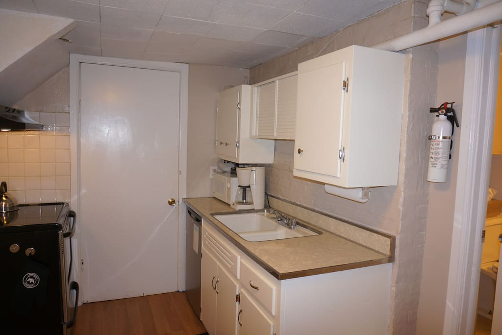 Galley kitchen with basic cooking equipment. Microwave, refrigerator, coffeemaker, toaster, full sized stove and oven.