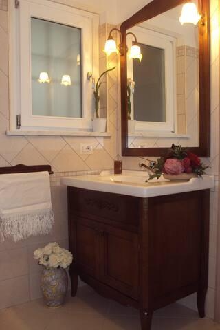 Bagno con doccia in cristallo e mobile in legno