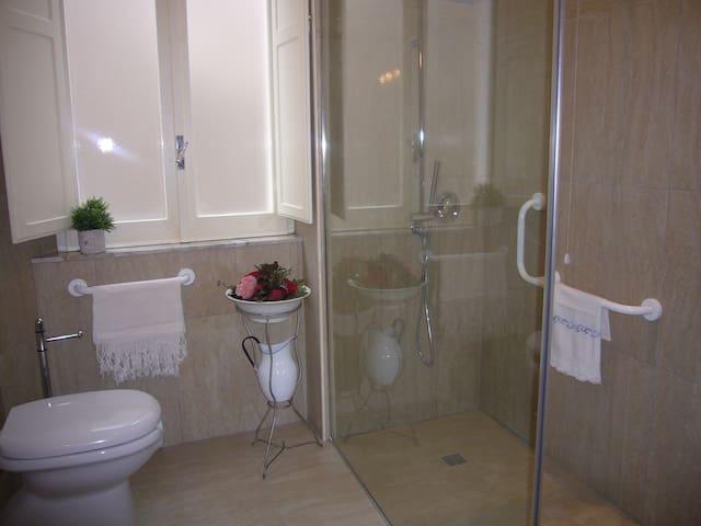Bagno grande e confortevole con enorme doccia di cristallo a pavimento