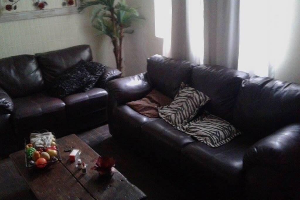 Sala com 2 sofás em couro, muito confortáveis e charmosos.