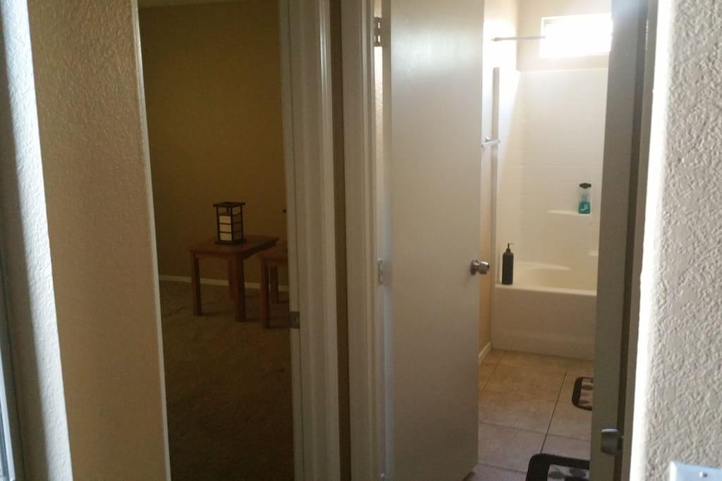 Front door view.  Empty bedroom and common bathroom.