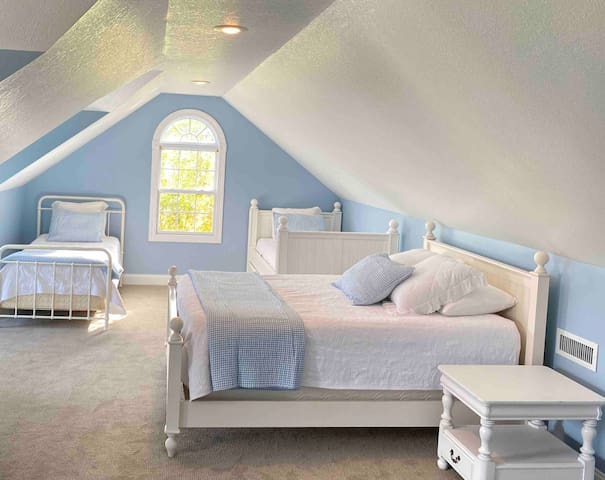 staircase near the master leads to this giant newly carpeted bonus room above the garage with a queen sized bed, twin day bed with pull out trundle, additional twin, and lots of space for kids to put sleeping bags or air mattresses.