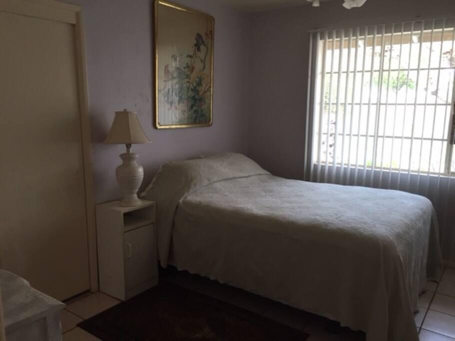 Queen-size bed with bedding, sliding door closet, dresser and desk. Room attached to adjacent bathroom.