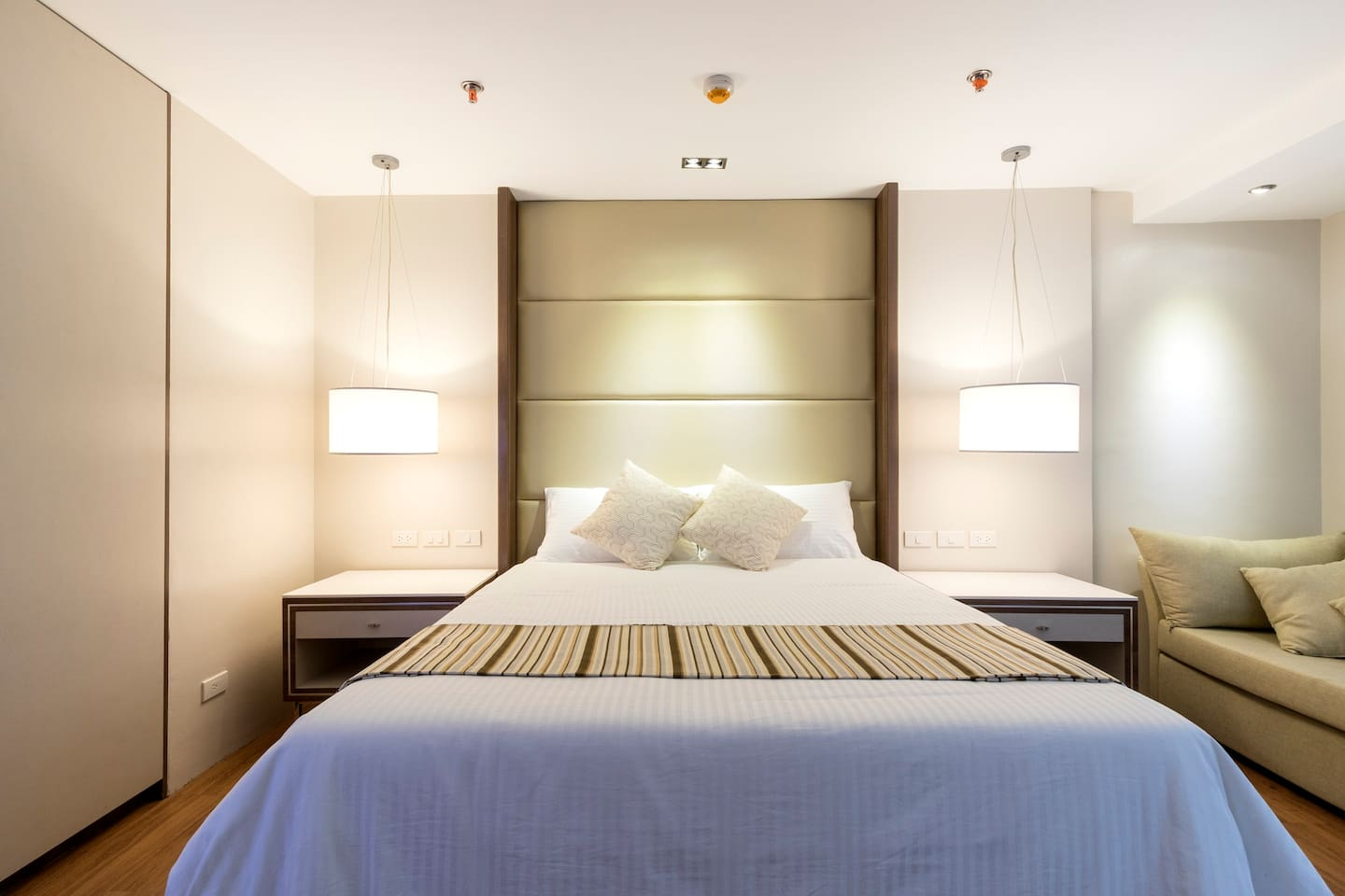 Queen size bed with padded headboard. Pendant light switches and socket are located above the 2 side tables.