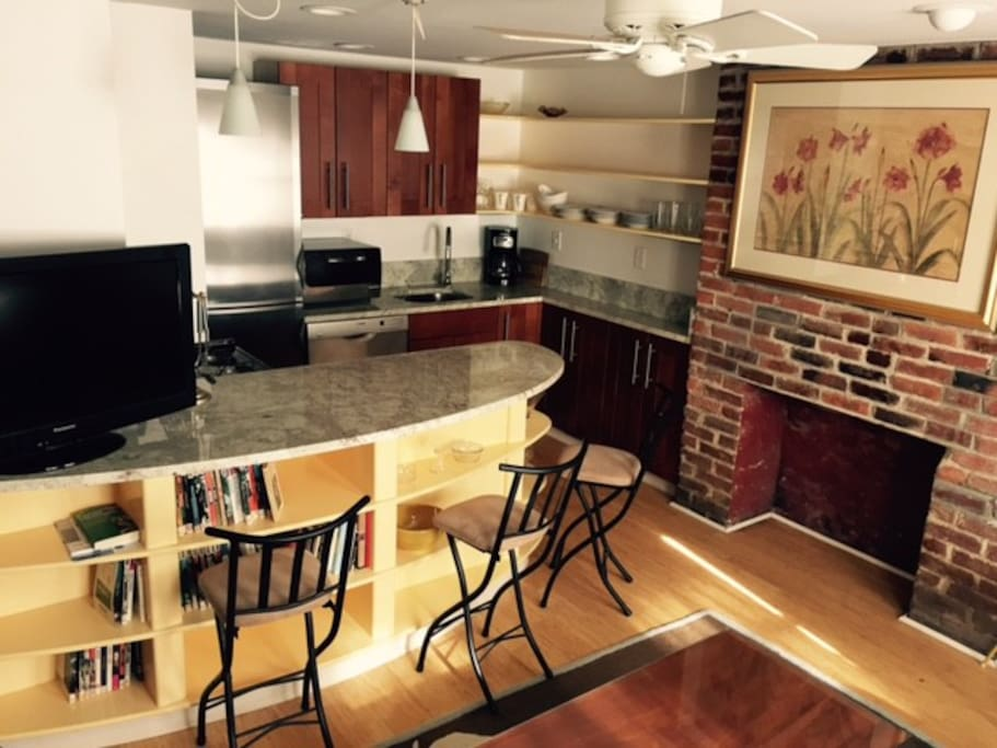 Fully equipped kitchen has custom island with seating for 4, flat screen TV, library.