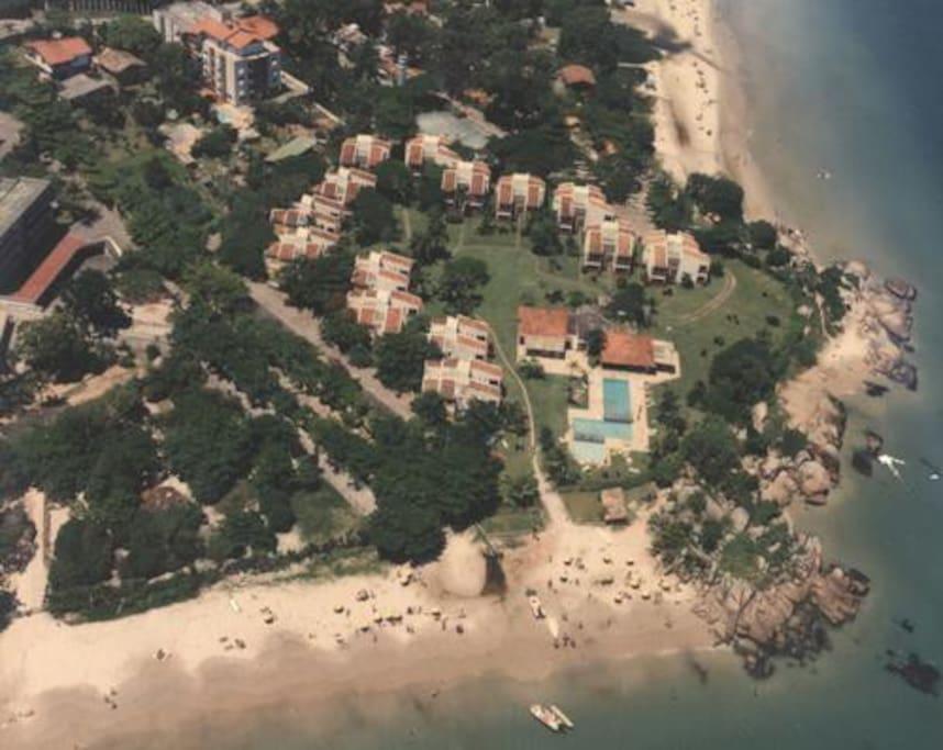Vista aérea dos apartamentos, piscinas e área verde junto ao mar. Praia privativa
