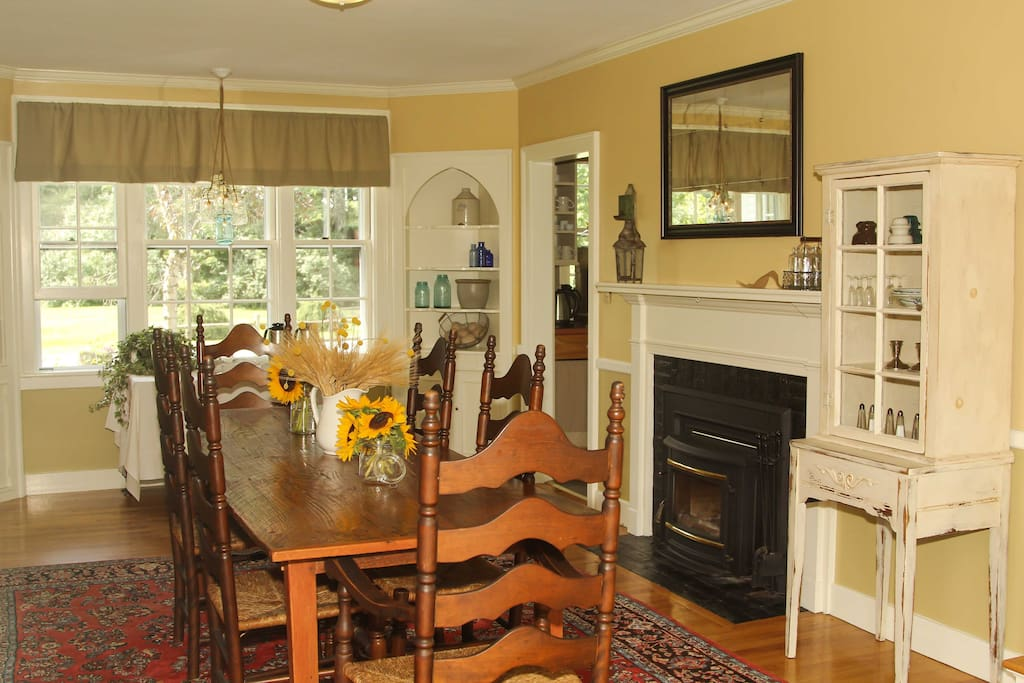 Our dining room features antique furniture and a working fireplace. An additional sun porch for dining is attached but not seen here.