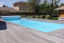 belle piscine avec chaises longues et bains de soleil très modernes et confortables