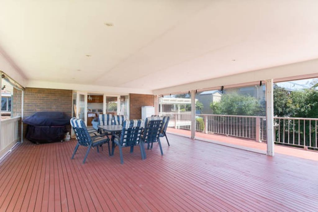 outdoor undercover Barbeque area with outdoor fridge and dining setting, overlooking pool