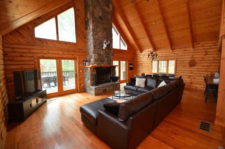 """Spacious living room with cathedral ceilings, a 65"""" TV and river rock fireplace"""
