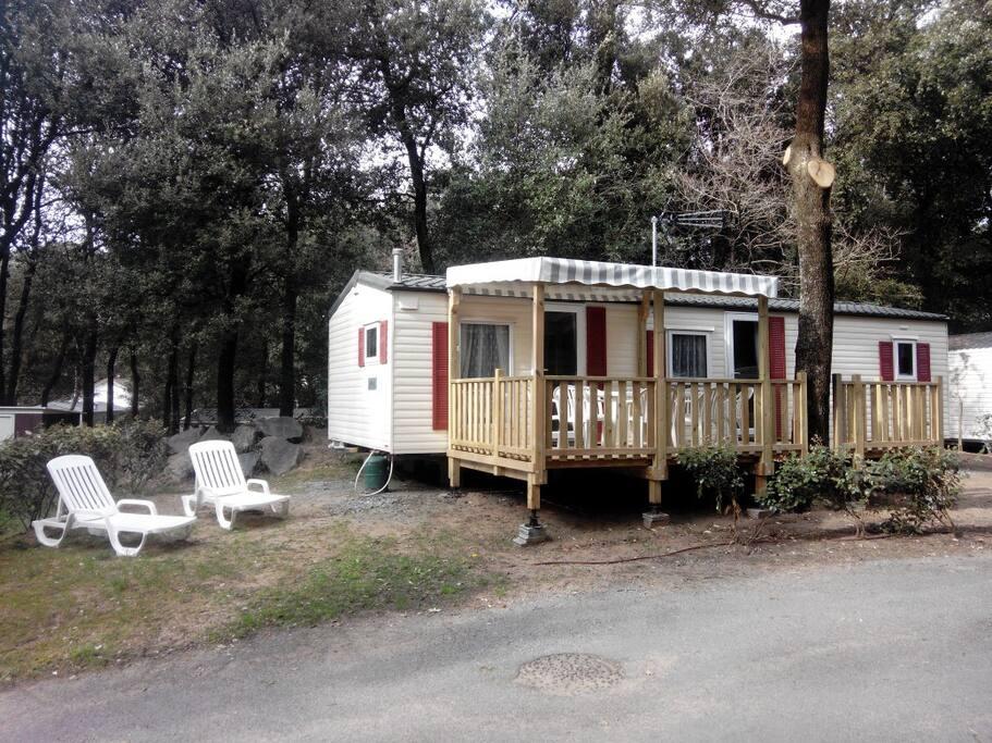 Vue extérieure sur le mobile-home, sa terrasse et son environnement