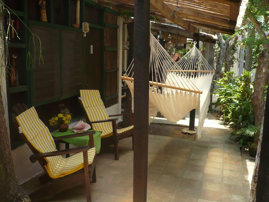 Porch con dos sillas y hamaca en cada Cabaña
