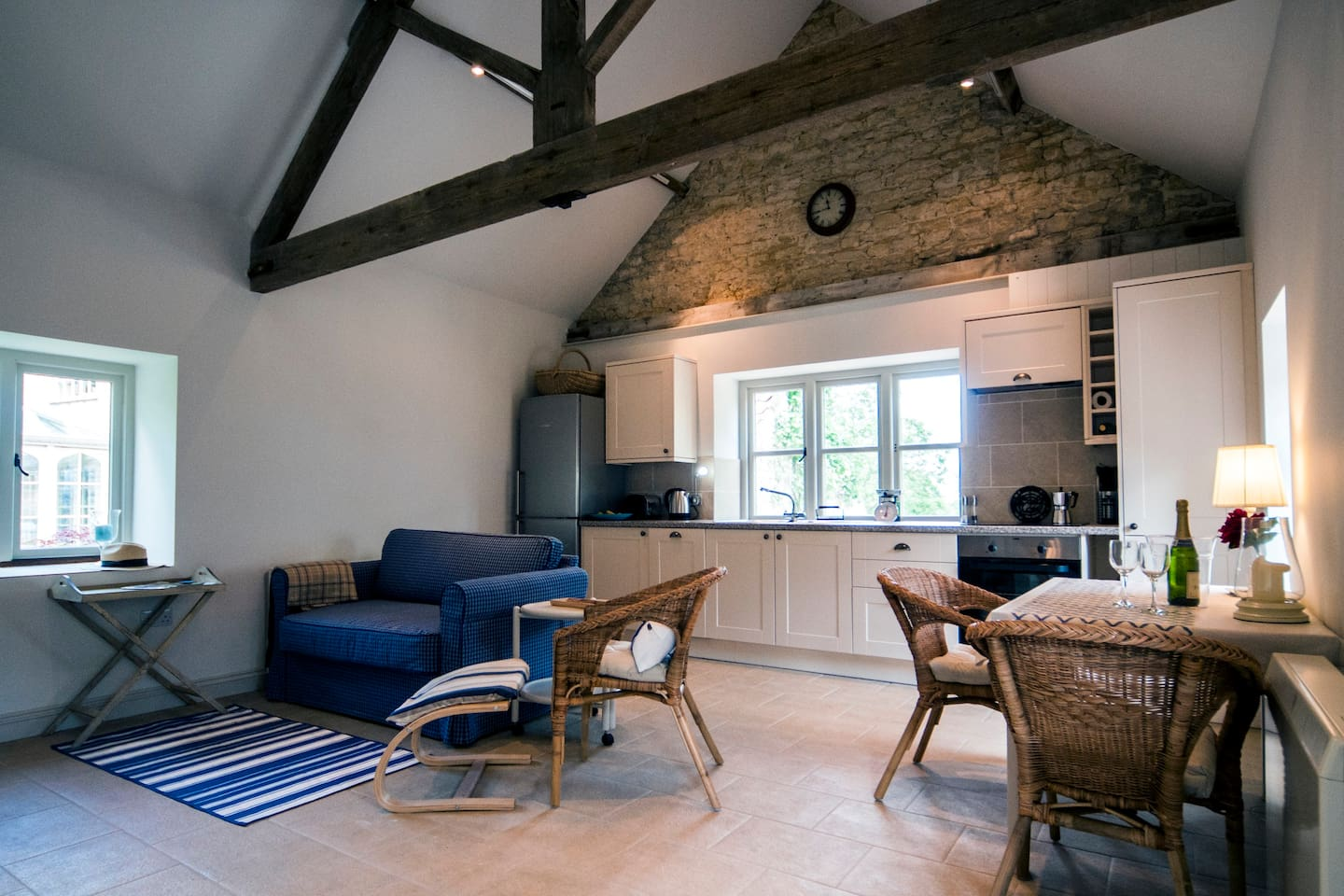 This is the sitting area with an AGA woodburner and windows on 3 sides. The stone wall and beams are original.