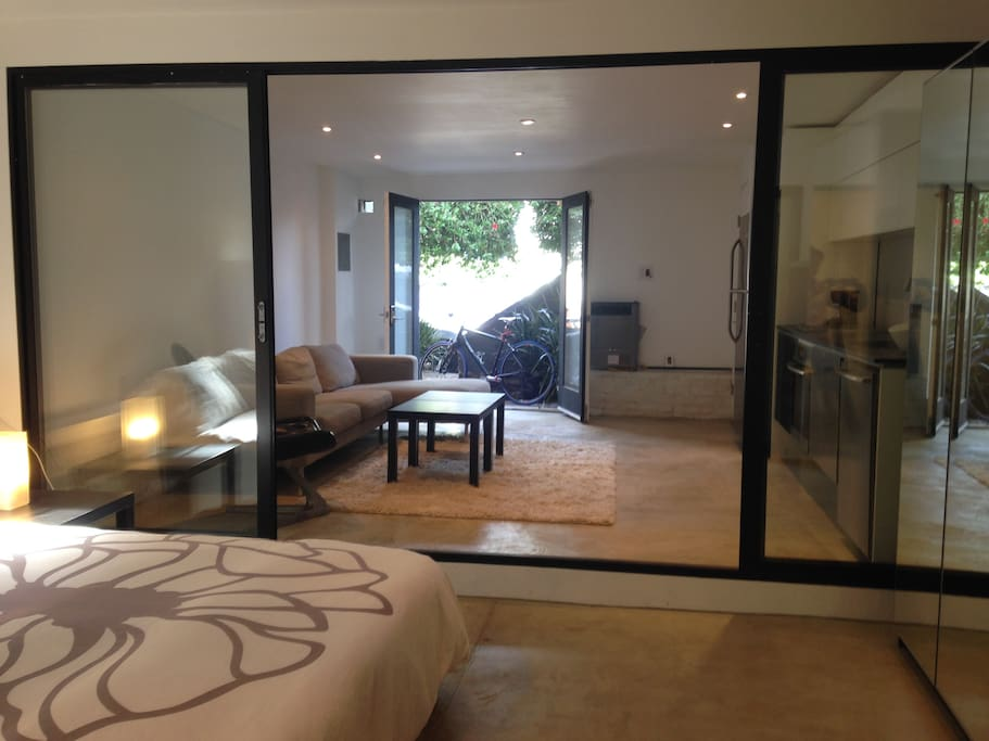 From bedroom, looking onto living and kitchen area, and front entrance with double glass doors. Glass sliding doors separate bedroom from living area and kitchen. Curtains between bedroom and living/kitchen area have been added for additional privacy.