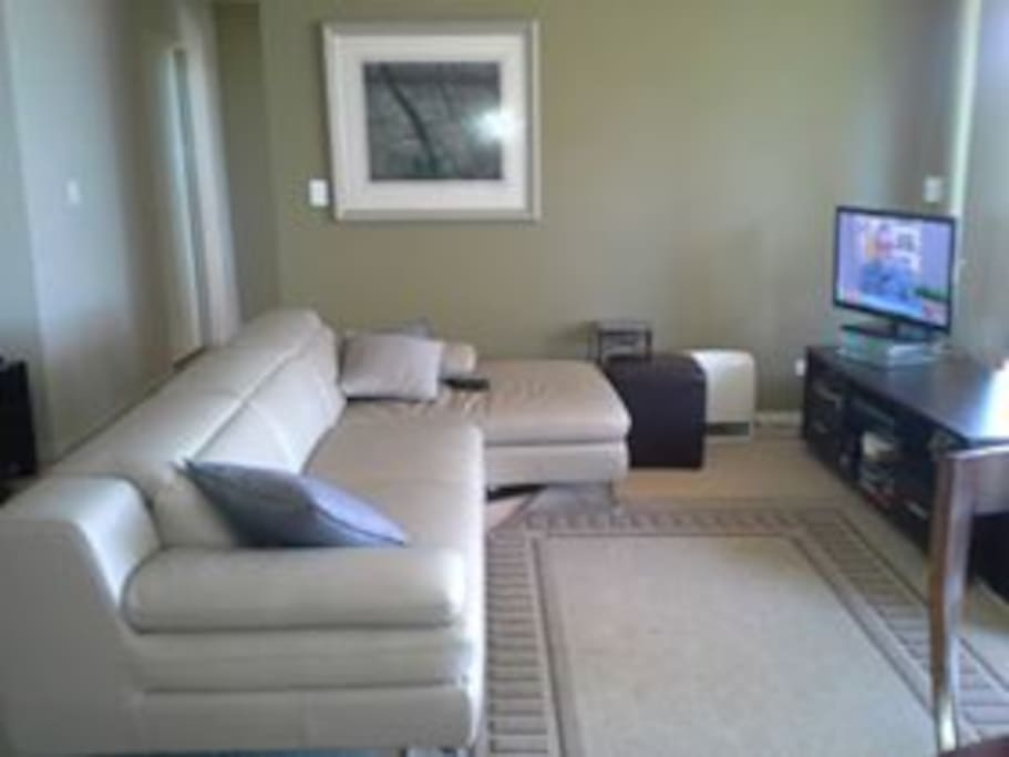 The lounge room has a large leather L shape lounge suite, entertainment unit and flat screen tv