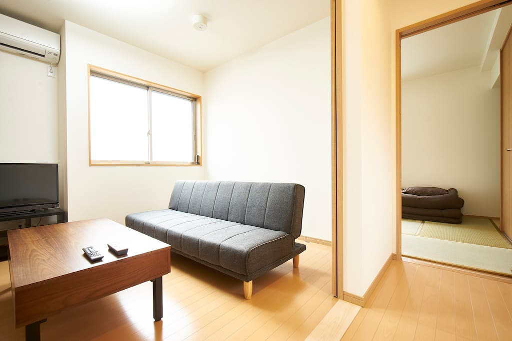 Living room with terrestrial Japanese TV available. Sofa turns into a bed.