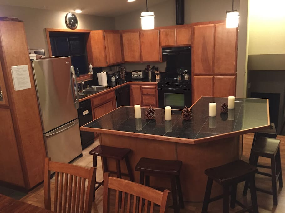 Full kitchen with open floor plan / large island / stainless steel appliances / gas range