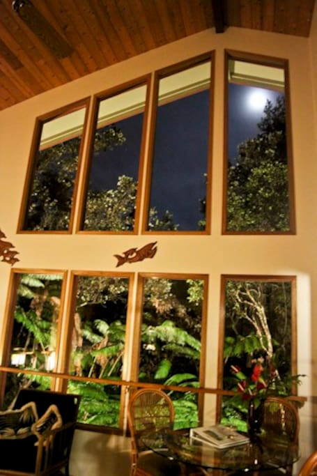 A glimpse of the full moon out of the floor to ceiling windows. The forest is lighted all around the exterior.