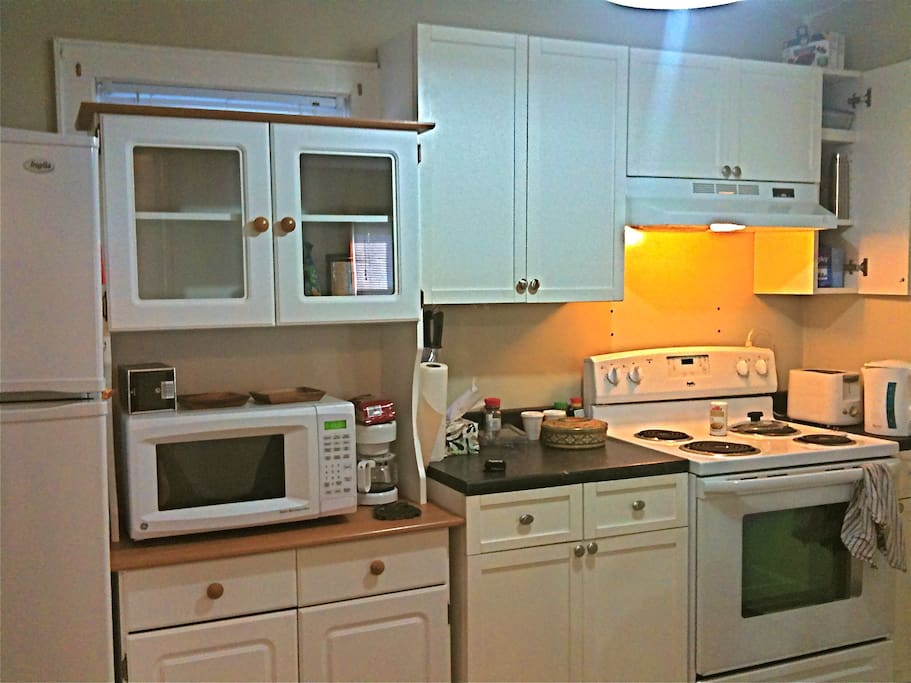 Full Kitchen with electric range, oven, microwave, toaster, coffee maker, kettle and fridge
