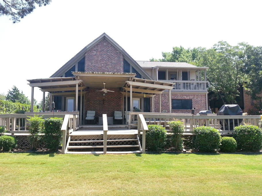 Back of house with large covered deck and multiple seating areas overlooking the lake.