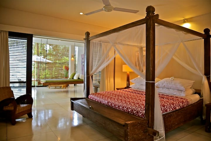The downstairs bedroom  has both AC and fan, as well as wooden louvred doors to keep you comfortable