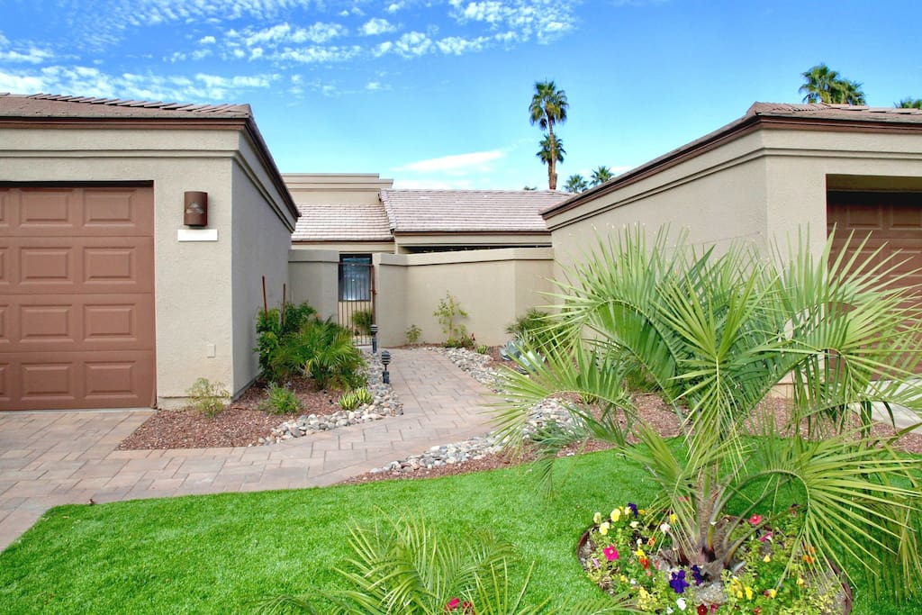 Lovely landscaped entrance leads up to your private, gated front patio.